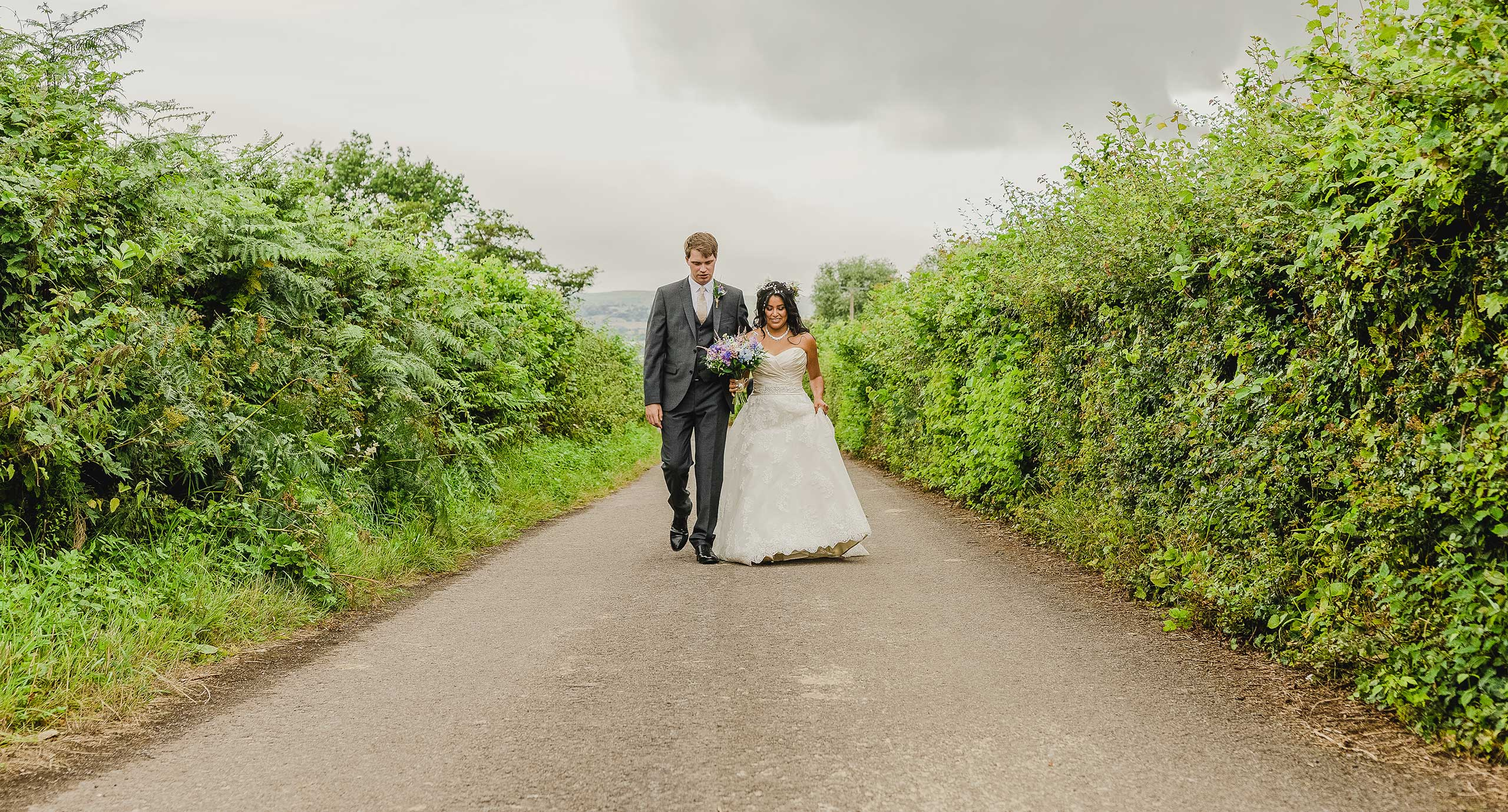 Bride and Groom walk to their wedding reception in Abergavenny. Natural wedding photography in South Wales