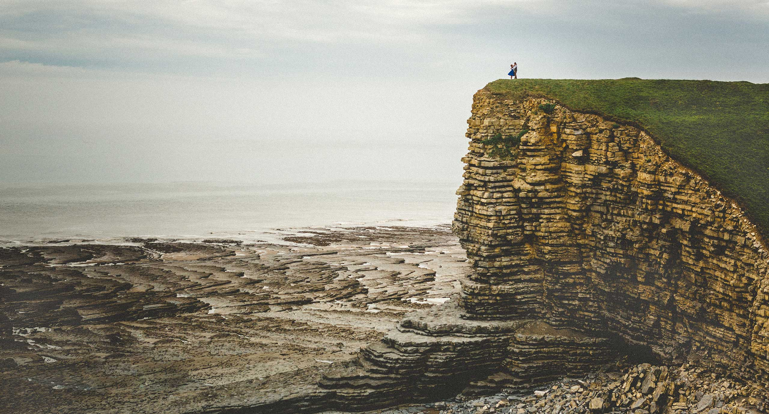 Wedding photography at Nash Point Lighthouse. Bride and Groom kiss on the edge of a cliff at Marcross Beach in South Wales