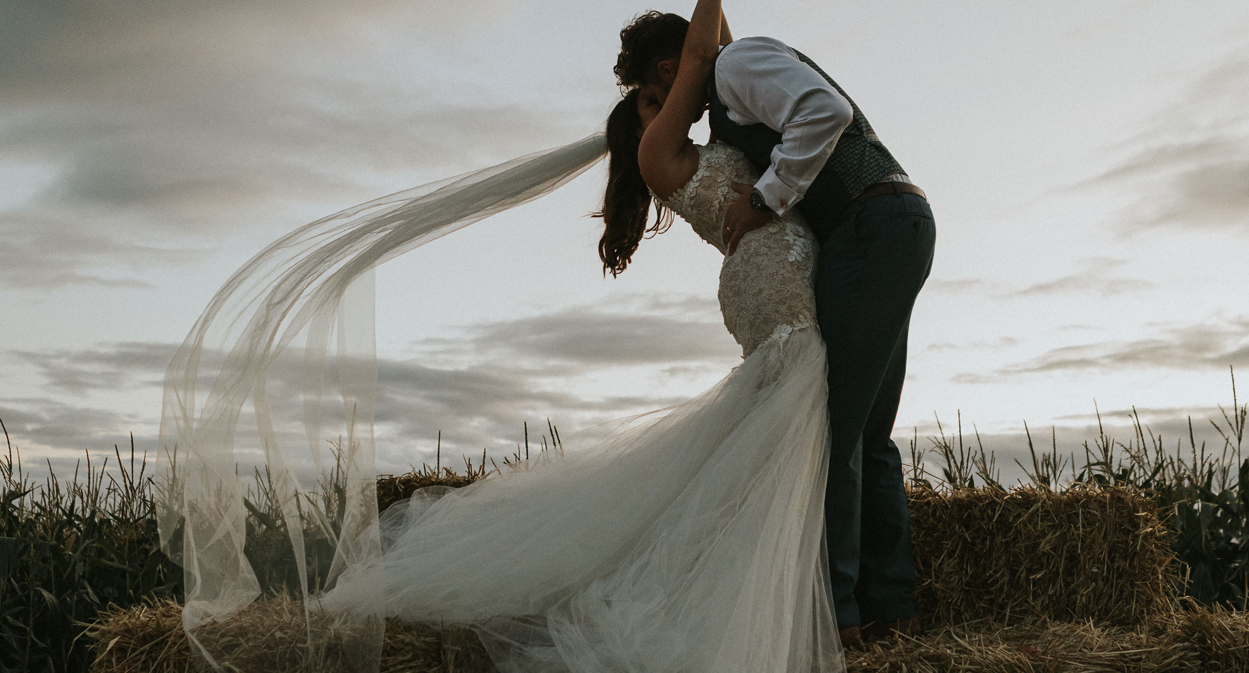 wedding-llantwit-major - Boho wedding South Wales - Bride and Groom kiss on a bale of hay