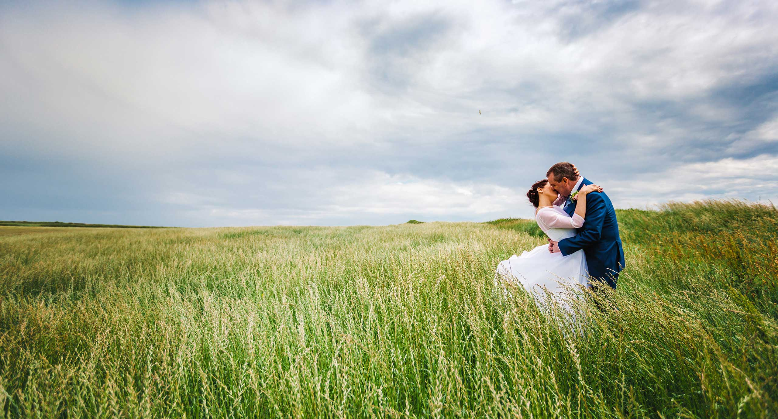 Wedding photography at Nash point Lighthouse. Bride and Groom kiss on the cliffs
