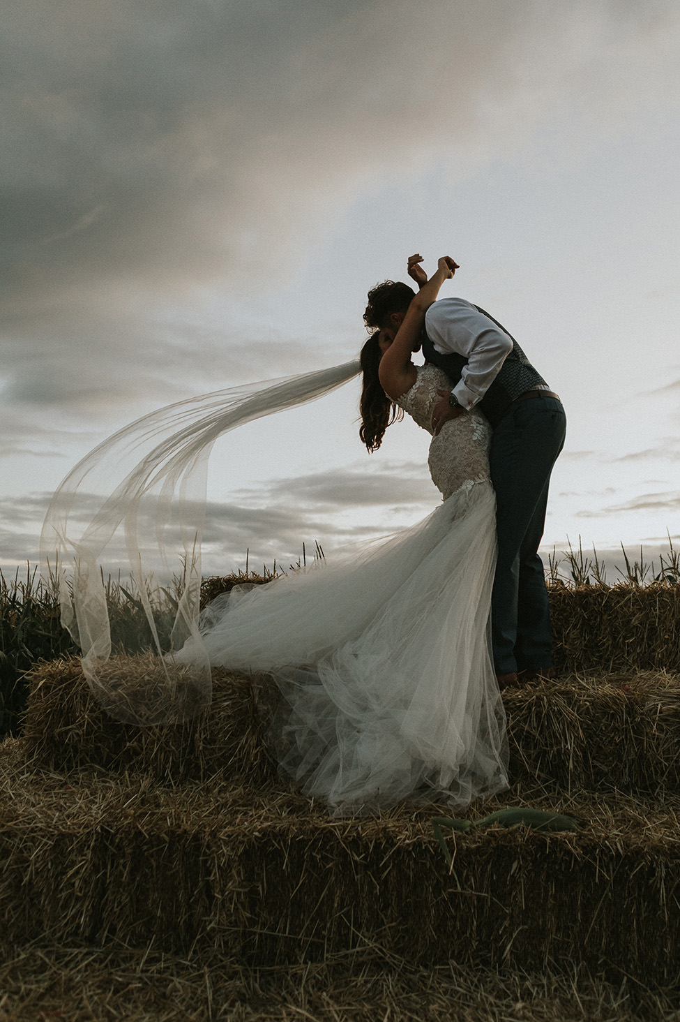 boho wedding south wales - Bride and Groom on bale of hay