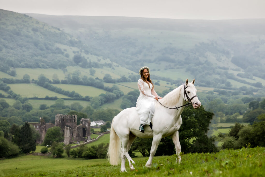 Boho farm wedding Wales - Bride arrives on white horse